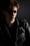 Un giovane in rivestimento di cuoio ed occhiali da sole Fotografia Stock Libera da Diritti