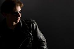 Un giovane in rivestimento di cuoio ed occhiali da sole Fotografia Stock