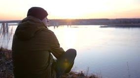 Un giovane in un rivestimento ed in un cappello si siede sulla sponda del fiume vicino al ponte ed ammira il bello tramonto Movim stock footage