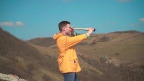 Un giovane in un rivestimento giallo, blue jeans si siede su una roccia e esamina un cannocchiale Il fondo ? montagne e cielo archivi video