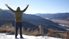 Un giovane in un rivestimento, stante sopra una montagna, esamina fuori la distanza e ritiene la libertà e la gioia dalla a stock footage