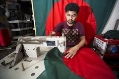 Un giovane sarto Md Rashed Alam, invecchia 28 bandiere nazionali del Bangladesh di fabbricazione a Dacca, Bangladesh Immagine Stock