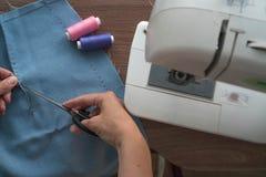 Un giovane sarto, una cucitrice, taglia i fili nella cucitura d'unto della tintura della gonna tagliata Vicino ? una macchina per immagine stock
