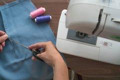 Un giovane sarto, una cucitrice, taglia i fili nella cucitura d'unto della tintura della gonna tagliata Vicino ? una macchina per fotografie stock
