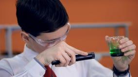 Un giovane scienziato illumina un prodotto chimico con una torcia elettrica stock footage