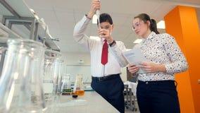 Un giovane scienziato mostra come utilizzare una pipetta elettronica stock footage