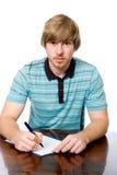 Un giovane si siede ad uno scrittorio con una penna a disposizione. Immagini Stock Libere da Diritti