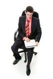 Un giovane si siede e lavorando ad un taccuino. Fotografie Stock