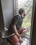 Un giovane si siede su un davanzale da una finestra aperta, tiene uno smartphone in una mano e gli altri tocchi ed esamina un ram fotografia stock