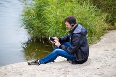 Un giovane si siede sulla sponda del fiume con un telefono ed ascolta musica con le cuffie Immagini Stock