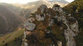Un giovane si siede in una posizione di loto sopra una roccia nelle montagne e medita Siluetta dell'uomo Cowering di affari volo  video d archivio