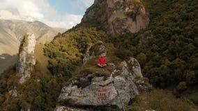 Un giovane si siede in una posizione di loto sopra una roccia nelle montagne e medita Siluetta dell'uomo Cowering di affari Volo  stock footage