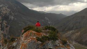 Un giovane si siede in una posizione di loto sopra una roccia nelle montagne e medita Siluetta dell'uomo Cowering di affari volo  archivi video
