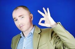 Un giovane sicuro in un cappotto crema mostra il gesto e gli sguardi di Okey alla macchina fotografica Concetto dei segni e Gestu immagini stock