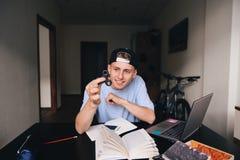 Un giovane sorridente gioca un filatore del dito nella sua stanza allo scrittorio Fotografia Stock