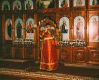 Un giovane sottopeso censes l'incensiere prima dell'altare alla liturgia divina nella chiesa ortodossa Fotografia Stock