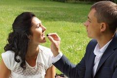 Un giovane sta alimentando la sua sposa con l'uva su un picnic nel parco immagine stock libera da diritti
