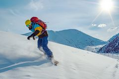 Un giovane sta guidando uno snowboard Neve non trattata nelle montagne immagini stock libere da diritti