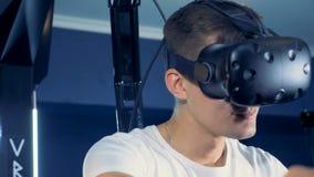 Un giovane sta indossando la cuffia avricolare di realtà virtuale e sta giocando un gioco di 360 realtà virtuali stock footage