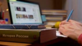 Un giovane sta sedendosi ad una tavola e sta scrivendo in un taccuino archivi video