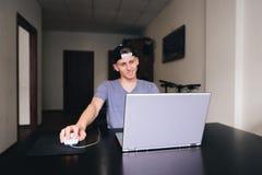 Un giovane sta sedendosi a casa per un computer portatile Fuoco sul computer portatile Fotografia Stock