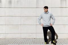 Un giovane sta su un fondo leggero del recinto Immagine Stock