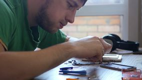 Un giovane stregone maschio abile in dettaglio piccoli del telefono rotto, vuole ripararlo 3840x2160 4K stock footage