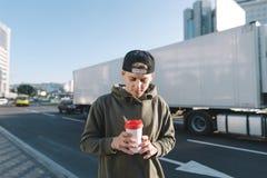 Un giovane, studente alla moda che sta nella via e che esamina una tazza di caffè in sue mani Lo studente sta contro un bordo del Fotografie Stock