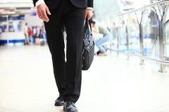 Un giovane studente bello dell'uomo d'affari in un vestito, viene con una cartella, alla stazione, aeroporto Concetto - un nuovo Fotografia Stock