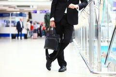 Un giovane studente bello dell'uomo d'affari in un vestito, viene con una cartella, alla stazione, aeroporto Concetto - un nuovo Immagini Stock Libere da Diritti