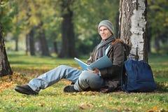 Un giovane studente sorridente ha messo su un'erba verde e sulla lettura della BO Fotografia Stock Libera da Diritti