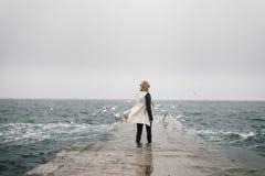 Un giovane studente sta camminando indietro su un pilastro umido ed esamina Fotografie Stock