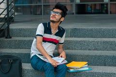 Un giovane studente in una maglietta si siede con i libri sulle scale Immagini Stock
