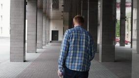 Un giovane studente va all'università l'uomo biondo sta andando un uomo cammina fra le colonne in sue mani video d archivio