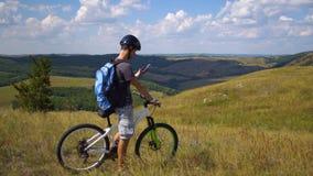 Un giovane su una bicicletta è guidato dal terreno facendo uso di una mappa sul suo telefono cellulare Immagine Stock Libera da Diritti