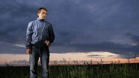 Un giovane sveglio ondeggia fuori dalle zanzare al tramonto sul campo Bello cielo su un fondo video d archivio