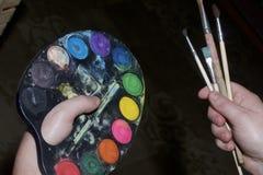 Un giovane tiene nelle sue pitture e spazzole delle mani per disegnare Fotografie Stock Libere da Diritti