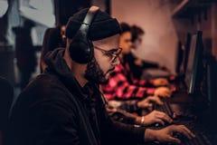 Un giovane tipo afroamericano, godente spendendo tempo con i suoi amici, giocanti in un video gioco con diversi giocatori su un P immagini stock libere da diritti
