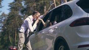 Un giovane tipo alla moda in una camicia bianca, in bretelle ed in una cravatta a farfalla rossa sta vicino all'automobile e baci stock footage