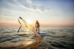 Un giovane tipo, un atleta alza una vela su un fare windsurf Immagini Stock Libere da Diritti