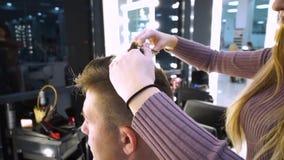 Un giovane tipo bello in un salone di bellezza Il tipo sta sedendosi nella poltrona Il parrucchiere taglia i suoi capelli Il tipo stock footage