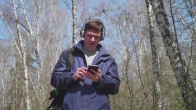 Un giovane tipo cammina nel parco, ascoltante la musica tramite le cuffie Passeggiata di mattina nell'aria fresca in primavera video d archivio