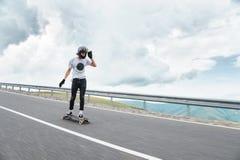 Un giovane tipo in un casco del interamente fronte sta guidando su una strada campestre all'alta velocità nella pioggia Fotografia Stock Libera da Diritti