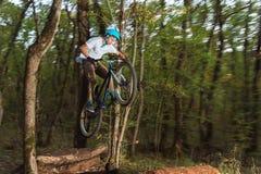 Un giovane tipo in un casco vola su una bicicletta dopo il salto da un estrattore a scatto fotografie stock libere da diritti