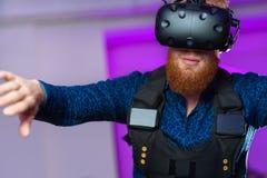 Un giovane tipo, con una barba rossa, sta giocando i giochi di realtà virtuale fotografia stock