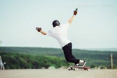 Un giovane tipo esegue un trucco complesso sul longboard Fotografia Stock Libera da Diritti
