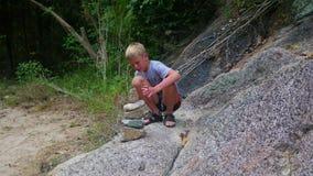 Un giovane tipo fa una scultura delle pietre dell'equilibrio Sport esterni stock footage