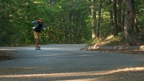 Un giovane tipo impara guidare un longboard È situato nella foresta vestita in una camicia di plaid ed in un cappello di feltro a archivi video