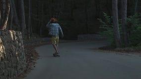 Un giovane tipo impara guidare un longboard È situato nella foresta vestita in una camicia di plaid ed in un cappello di feltro a stock footage