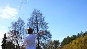 Un giovane tipo nel parco fa le grandi bolle di sapone Festa e spettacolo all'aperto stock footage